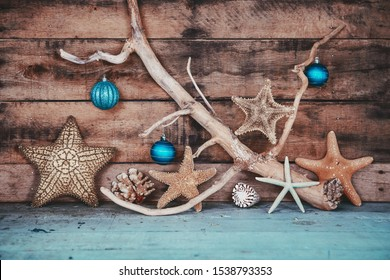 Beachy scene of starfish and teal ornaments for Christmas on a wooden background