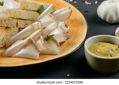 Beacon Axunge with bread and garlic on dark background