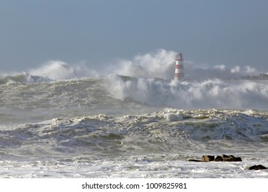 Beacon and pier of Povoa do Varzim e Vila do Conde fishing harbor and marina under heavy storm with strong wind and big waves, north of Portugal.