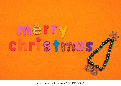 A Bead Christmas tree and Merry Christmas on an orange background