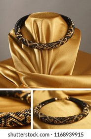 Bead rope, seed beads, bead necklace. Black bead necklace on a gold satin on gray background