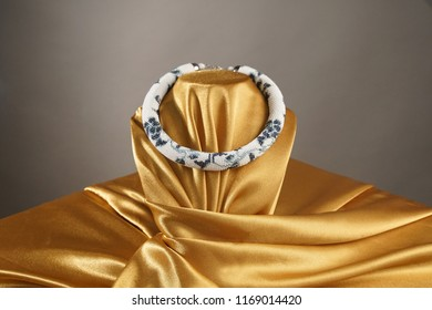 Bead rope, seed beads, bead necklace. White bead necklace on a gold satin on gray background