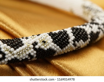 Bead rope, seed beads, bead necklace. Close up of white and black bead necklace on a gold satin