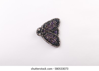 A beaded brooch in the form of flies