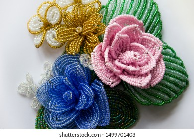 Beaded flowers on a white background. Blue bead flower, pink bead flower, yellow bead flower. Flowers from beads. Three flower from beads on a white background.