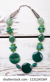 Beaded necklace with green polished stones. Close up expensive unusual jewellery.