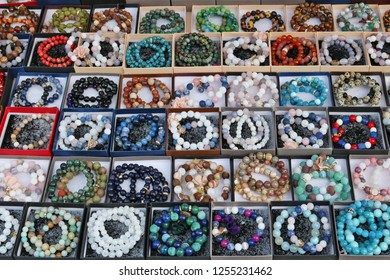 Beads and bracelets made of round stones and glass are sold on the street during the fair. Mass no name production