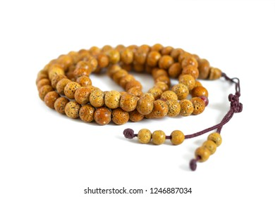 Beads of a Buddhist monk from the textured bones of bird cherry, strung on a brown thread, isolated on a white background