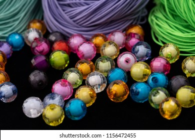 Beads, colorful beads on a black background. Elastic rope on the background.