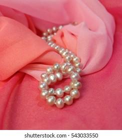 Beads of pearl on pink chiffon fabric.
