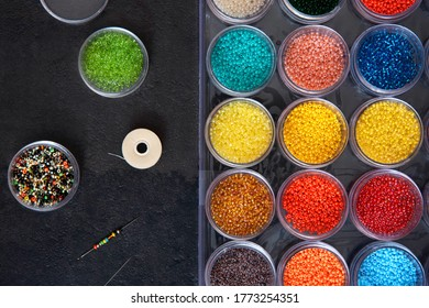 Beads with thread and needle for needlework .Beads in a box of different colors. Top view.