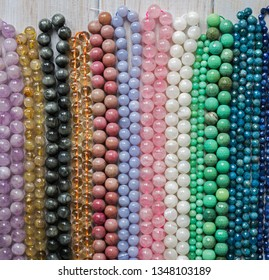 Beads from various natural stones are strung on threads.