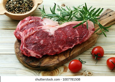 Beaf steak with rosemary on wooden chopping board