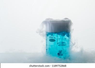 Beaker with blue liquid engender white smoke. Dry ice effect