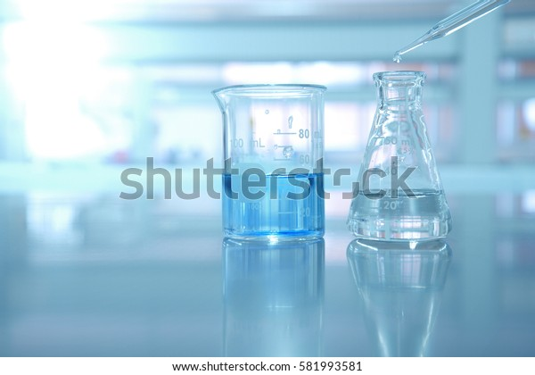 beaker and flask with blue solution and drop of water in science background
