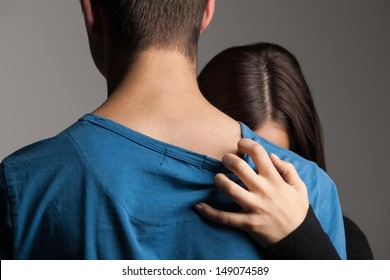 Beak-up. Young couple hugging while isolated on grey