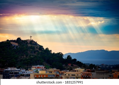 Beam of light through the clouds over a cross on top of the hill. Rays of light shining through clouds. Celestial entity over a hill with a crucifix that protects the city. Cross silhouette.