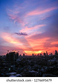 The beam of light through the  pink cloud and blue sky to the skyscrapers in downtown Bangkok cityscapes, the capital of Thailand in southeast Asia, with golden sunshine evening in vertical view.