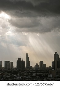 The beam of light through the rain cloud to the skyscrapers in downtown Bangkok cityscapes, the capital of Thailand in southeast Asia, in vertical view.