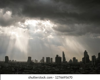 The beam of light through the rain cloud to the skyscrapers in downtown Bangkok cityscapes, the capital of Thailand in southeast Asia, in horizontal view.