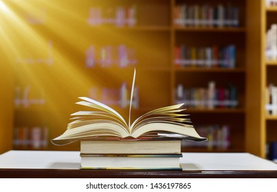 The beam shines down to the open magic book on wood table and blurred bookshelf in the library, education background.