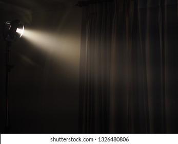 The beam from spotlight illuminates the curtains in the dark room.