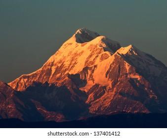 beam of sun light illuminating mountain with three peaks in Himalaya