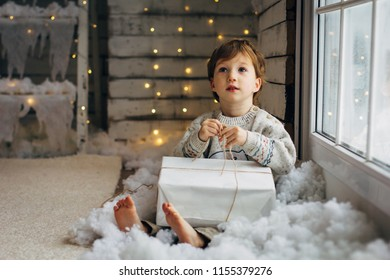 Beaming curlyhair boy opening his christmas gift. New Year lights background
