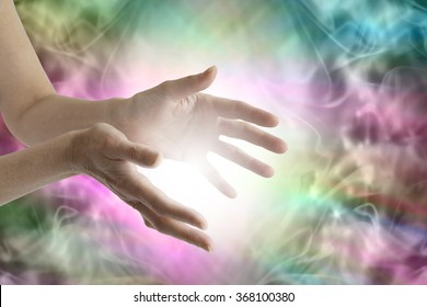 Beaming healing energy - Outstretched female healing hands with white light between and a vibrant multicolored flowing energy field background