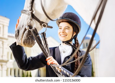 Beaming horsewoman. Beaming dark-haired horsewoman with long fishtail petting her white horse