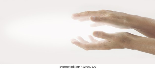 Beaming Reiki Healing Energy  -  Pair of female hands held parallel on a light background with white energy between palms