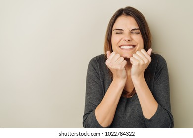 Beaming young woman screwing up her eyes and holding her fists to her chin in an expression of excitement over a white background with copy space