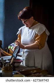 BEAMISH MUSEUM. CO DURHAM. ENGLAND. APRIL 9.  2017.   Woman in vintage costume working in old fashioned kitchen.   April 9, 2017. Beamish Open Air Museum, Co Durham, England, UK.