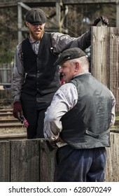 BEAMISH MUSEUM. CO DURHAM. ENGLAND. APRIL 9.  2017. Men in vintage working clothes holding a conversation.  April 9, 2017. Beamish Open Air Museum, Co Durham, England, UK.