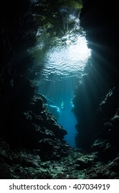 Beams of bright sunlight filter into the a dark, underwater cavern along the edge of a remote island in the Solomon Islands.