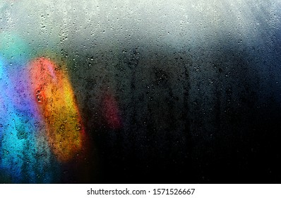 Beams of lights through a wet glass on a dark night, background of cold drops of water.
