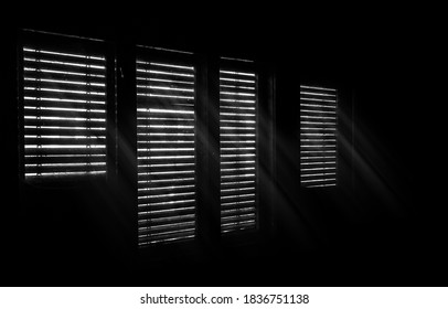 Beams of sunlight through old wooden blinds. Light coming through windows of an old abandoned house. Abstract background, black and white image.
