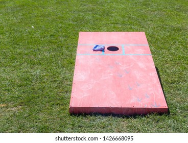 Bean Bag Toss Board:  Bean bag toss game board isolated on a loan of greeen grass.