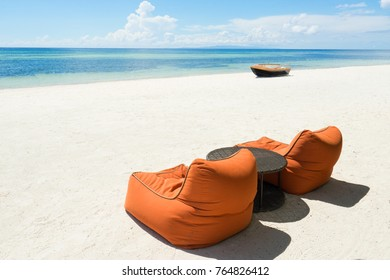 Bean bags and table on the beach.  Sea, blue sky and boat on background.
