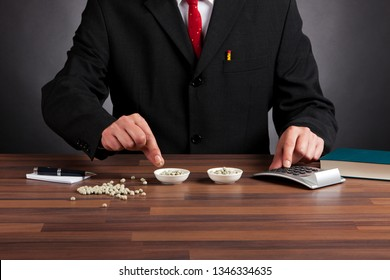 Bean counter  - accountant in business suit behind desk counting peas
