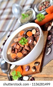Bean soup with large beans on cutting board, carrots, parsley, marjoram, spoon and ladle - vertical photo