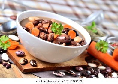 Bean soup with large beans on cutting board, carrots, parsley, marjoram, spoon and ladle, towel in background
