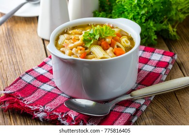 Bean soup with penne pasta in a white ceramic bowl.