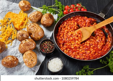 bean with tomato sauce in a skillet. baked potato or jacket potatoes with golden brown crispy skin on a paper with cheddar cheese at background, horizontal view from above, close-up