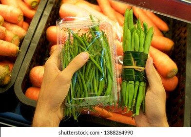 Beans bundled in a plastic package and other beans wrapped in Banana leaf held in female hands. This is an excellent solution how replace plastic packaging and reduce the waist of it - Bali, Indonesia