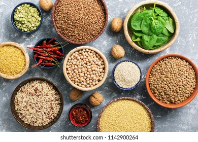 Beans, cereals, spinach, nuts and spices on a gray background. The concept of healthy eating. Healthy vegetarian food. Flat lay, copy space.