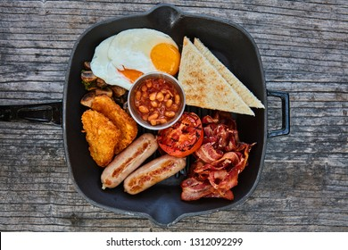 Beans, eggs, hashbrowns, sausages, bacon, fried mushrooms, grilled tomato served in a frying pan