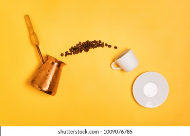 Beans falling from Turkish cezve into espresso cup on yellow, concept of coffee making and drinking, flatlay
