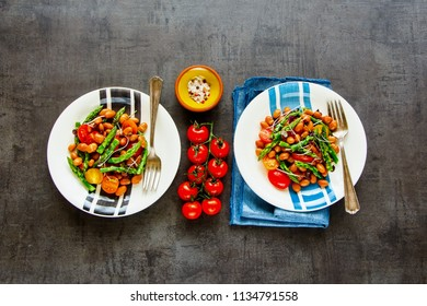 Beans salad plates with aspargus, micro greens and tomatoes flat lay. Vegan healthy energy boosting salad on dark background. Clean eating, superfood, vegan, detox food concept. Top view