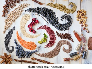 Beans, seeds and herbs forming swirls on a wooden table